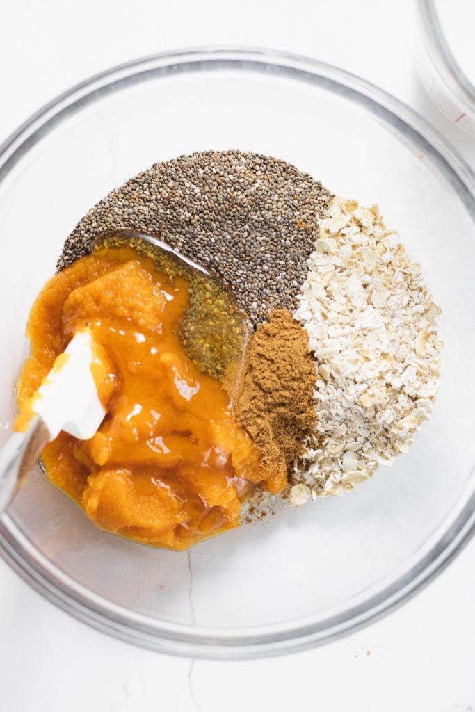 A glass bowl with chia seeds raw oats, pumpkin puree, pumpkin spice & honey.