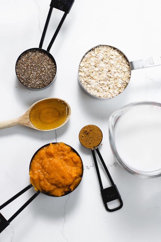 An overhead shot of the ingredients including chia seeds, oats, tablespoon of honey, teaspoon of pumpkin spice, a cup of cashew milk and half cup of pumpkin puree.
