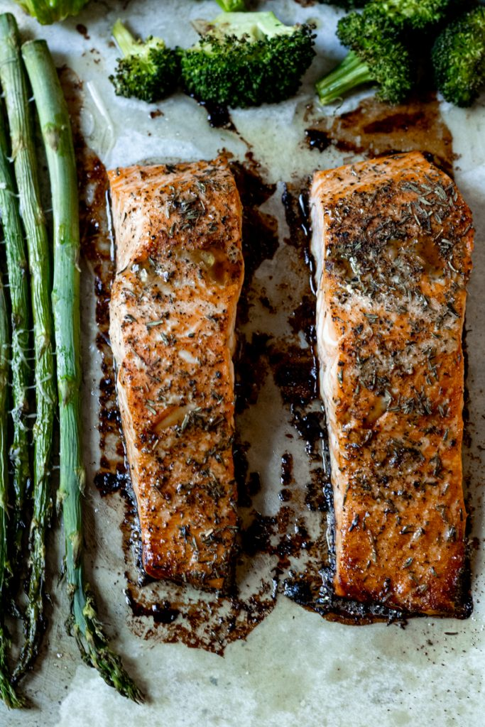 Two roasted salmon fillets on a baking sheet cooling with the asparagus and broccoli