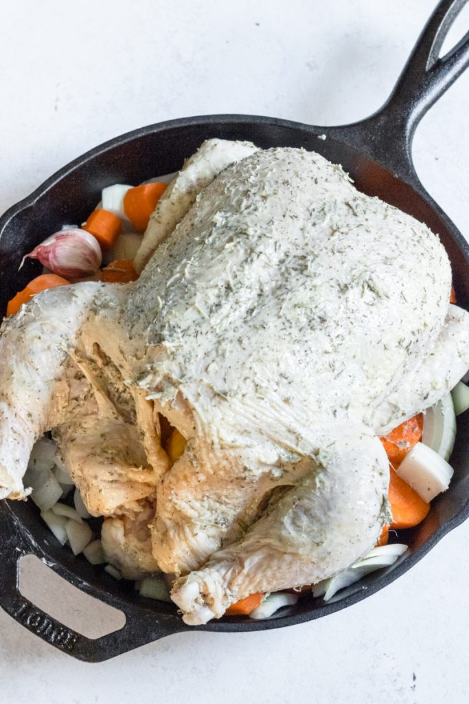 Prepped whole roasted chicken with butter and herbs sitting in a Lodge cast iron skillet.