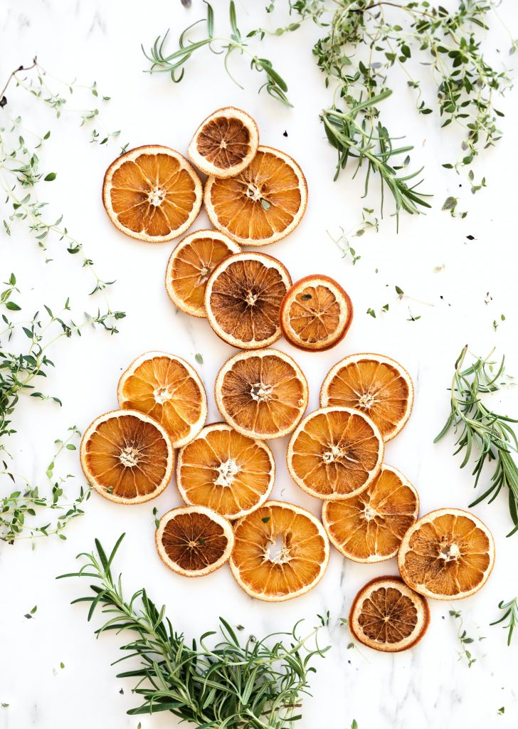 scattered orange slices and green herbs