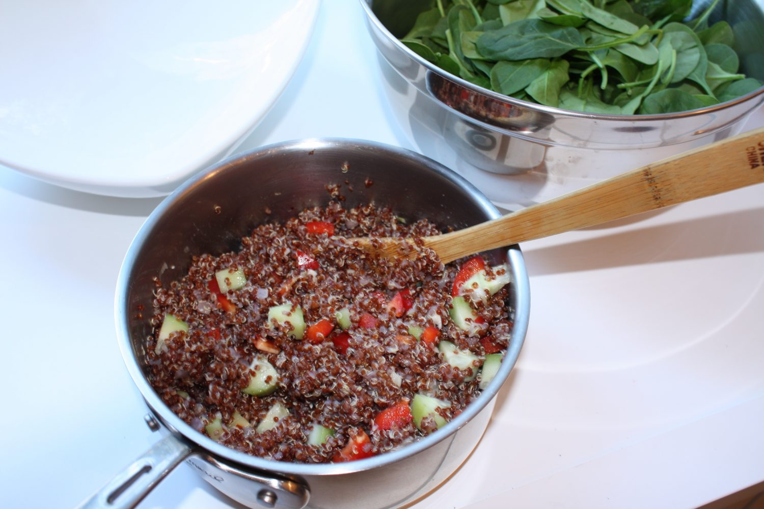 mixing vegetables with red quinoa