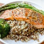One plated roasted salmon served over quinoa, asparagus and broccoli