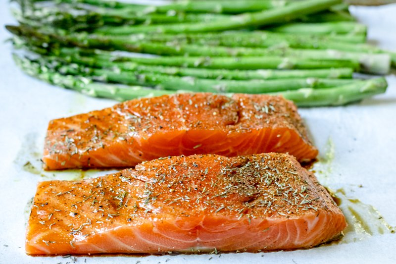 One sheet pan including two seasoned salmon fillets and raw asparagus