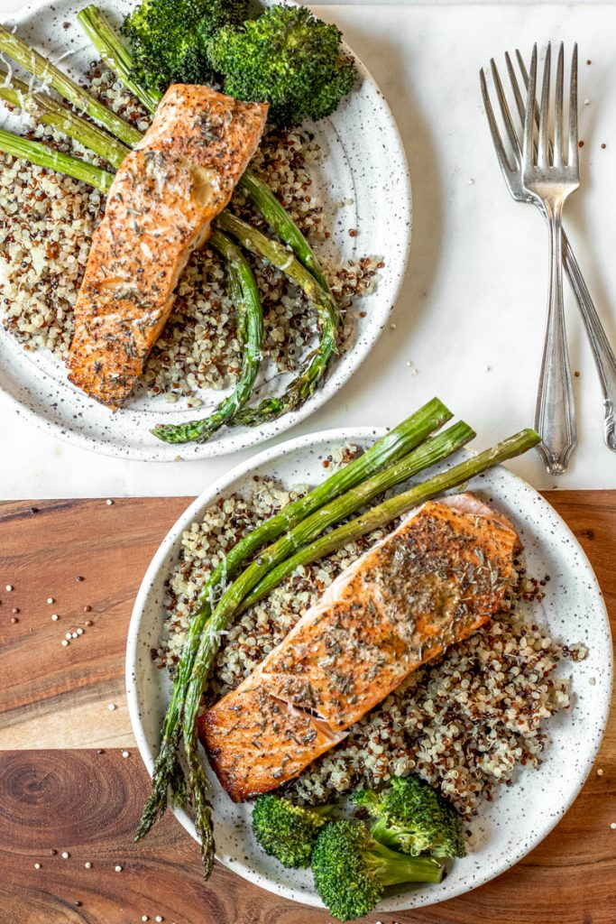 Two plated seasoned roasted salmon with quinoa, asparagus and broccoli