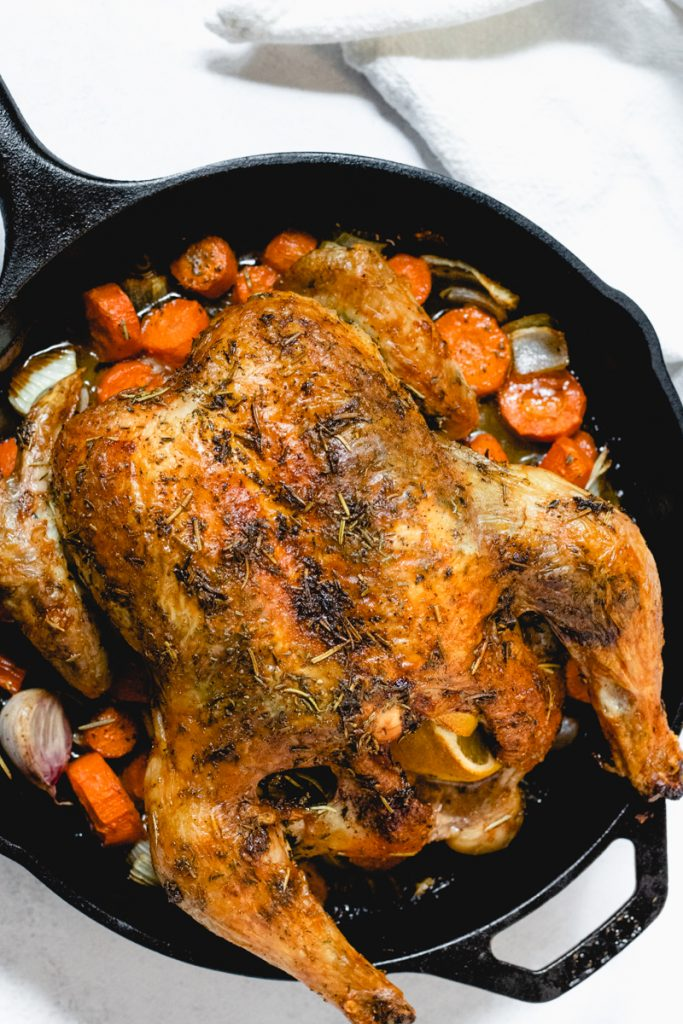 Whole roasted chicken sitting on top of roasted carrots and onions in a cast iron skillet.
